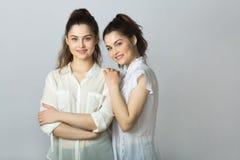 Dos muchachas gemelas de las hermanas hermosas en las blusas blancas Foto de archivo libre de regalías