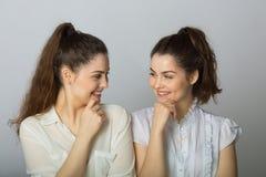 Dos muchachas gemelas de las hermanas hermosas en las blusas blancas Fotos de archivo