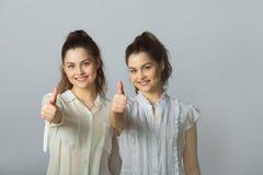 Dos muchachas gemelas de las hermanas hermosas en las blusas blancas Imágenes de archivo libres de regalías