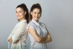 Dos muchachas gemelas de las hermanas hermosas en las blusas blancas Imagen de archivo