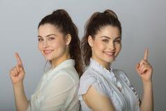 Dos muchachas gemelas de las hermanas hermosas en las blusas blancas Imagenes de archivo
