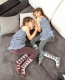 Dos muchachas gemelas que duermen en el sofá Imágenes de archivo libres de regalías