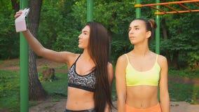 Dos muchachas hacen el feliz selfie de la aptitud Figuras de los deportes y buen humor almacen de metraje de vídeo