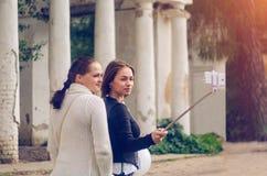 Dos muchachas hacen el selfie en ruinas del teléfono móvil cerca Fotos de archivo libres de regalías