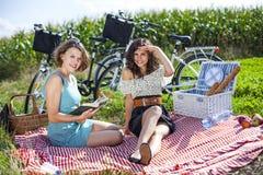 Dos muchachas hacen una comida campestre Foto de archivo libre de regalías