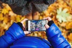 Dos muchachas hacen una foto de zapatos por el teléfono en parque del otoño Forma de vida y concepto de la tecnología Fotos de archivo libres de regalías