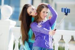 Dos muchachas hacen a uno mismo en la ciudad Imagen de archivo libre de regalías