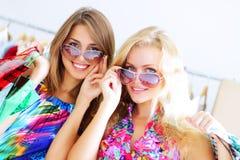 Dos muchachas hacia fuera que hacen compras Foto de archivo libre de regalías