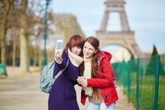 Dos muchachas hermosas alegres en París que toma el selfie Fotos de archivo libres de regalías