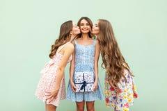 Dos muchachas hermosas besan a sus amigos adultos jovenes hermosos, enhorabuena con cumpleaños y dan una actual caja Fotografía de archivo