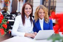 Dos muchachas hermosas con el ordenador portátil Foto de archivo libre de regalías