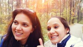 Dos muchachas hermosas con la cámara del teléfono celular que toma el selfie de las fotos en parque de la caída del otoño Imagen de archivo libre de regalías