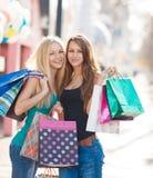 Dos muchachas hermosas con los panieres coloridos Imagen de archivo libre de regalías