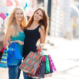 Dos muchachas hermosas con los panieres coloridos Foto de archivo