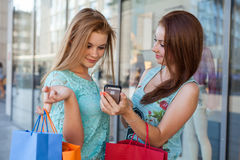Dos muchachas hermosas con los panieres coloridos y el teléfono móvil Imagen de archivo libre de regalías