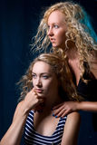 Dos muchachas hermosas contra un fondo oscuro Fotos de archivo