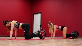 Dos muchachas hermosas de los deportes realizan un entrenamiento gordo-ardiendo activo que salta como un salto del kango en zapat metrajes