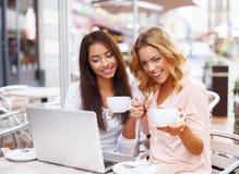 Dos muchachas hermosas en café con el ordenador portátil Fotos de archivo libres de regalías