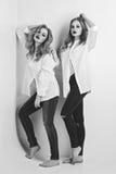 Dos muchachas hermosas en camisas y vaqueros de los hombres Imagen de archivo libre de regalías