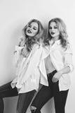 Dos muchachas hermosas en camisas y vaqueros de los hombres Fotos de archivo