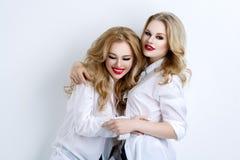 Dos muchachas hermosas en camisas y vaqueros de los hombres Imágenes de archivo libres de regalías