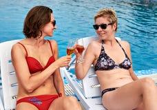 Dos muchachas hermosas en champán de consumición del bikini Imagen de archivo libre de regalías
