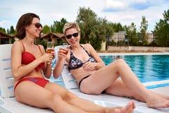 Dos muchachas hermosas en champán de consumición del bikini Imagen de archivo
