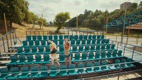 Dos muchachas hermosas en el día soleado tienen la diversión y baile en la gradería cubierta en slomo almacen de metraje de vídeo