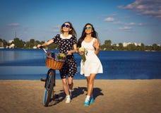 Dos muchachas hermosas en la playa con la bicicleta Fotografía de archivo libre de regalías
