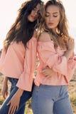 Dos muchachas hermosas en la presentación de la ropa casual al aire libre Imagen de archivo