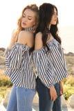 Dos muchachas hermosas en la presentación de la ropa casual al aire libre Foto de archivo libre de regalías