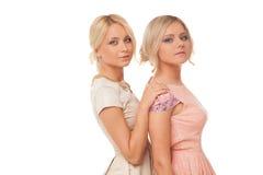 Dos muchachas hermosas en los vestidos de la moda aislados Imágenes de archivo libres de regalías