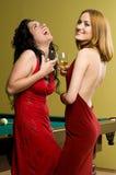 Dos muchachas hermosas en rojo con el coñac Fotografía de archivo libre de regalías
