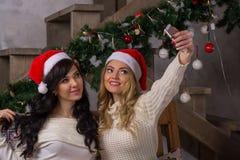 Dos muchachas hermosas en sonrisas de los sombreros de santa hacen selfies cerca del Ch Fotografía de archivo