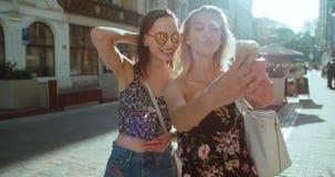 Dos muchachas hermosas jovenes que toman el selfie en una calle de la ciudad Imagen de archivo libre de regalías