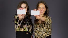 Dos muchachas hermosas muestran la tarjeta de visita en blanco almacen de video