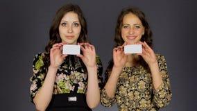 Dos muchachas hermosas muestran la tarjeta de visita en blanco almacen de metraje de vídeo