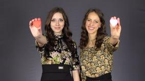 Dos muchachas hermosas muestran un corazón rojo almacen de video