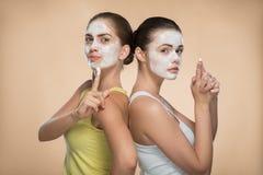 Dos muchachas hermosas que aplican la máscara poner crema facial y Foto de archivo libre de regalías
