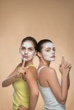 Dos muchachas hermosas que aplican la máscara poner crema facial y Imagen de archivo