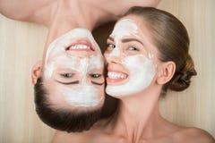 Dos muchachas hermosas que aplican la máscara poner crema facial y Imagen de archivo libre de regalías