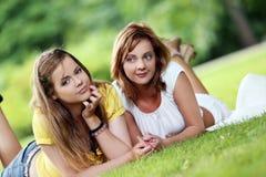 Dos muchachas hermosas que cuelgan en el parque Imagen de archivo libre de regalías