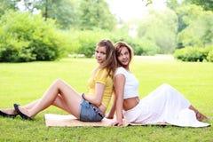 Dos muchachas hermosas que cuelgan en el parque Imágenes de archivo libres de regalías