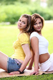 Dos muchachas hermosas que cuelgan en el parque Fotos de archivo