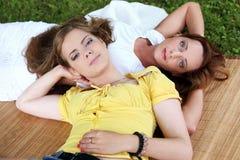 Dos muchachas hermosas que cuelgan en el parque Fotografía de archivo libre de regalías