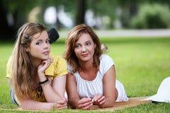 Dos muchachas hermosas que cuelgan en el parque Foto de archivo libre de regalías
