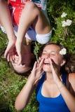 Dos muchachas hermosas que gritan y que miran para arriba al aire libre Foto de archivo