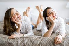 Dos muchachas hermosas que hablan y que sonríen mientras que miente en una cama Imagen de archivo libre de regalías