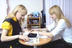 Dos muchachas hermosas que hacen la manicura fotos de archivo libres de regalías