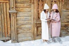 Dos muchachas hermosas que llevan invierno caliente visten la revista de la lectura al aire libre Imagen de archivo